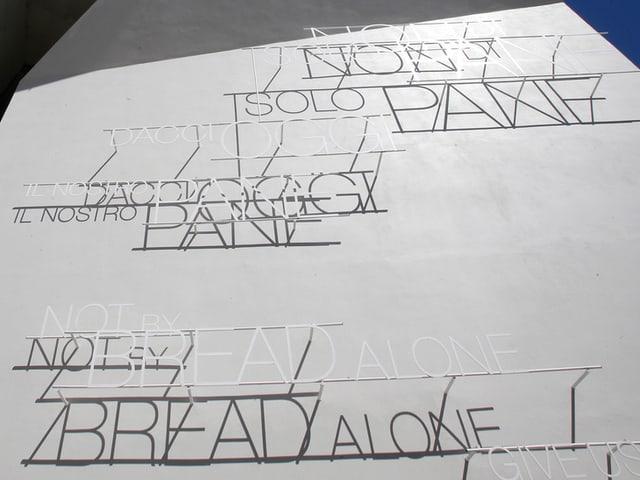 Graue Wand mit Aufschrift «nicht vom Brot allein» in verschiedenen Sprachen