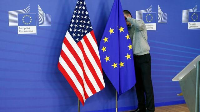 Die Amerikanische und die EU-Flagge nebeneinander. Die EU-Flagge wird von einem Mann gerichtet.