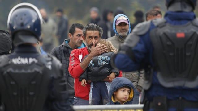 Bosnische Polizisten mit Migranten an der kroatischen Grenze.
