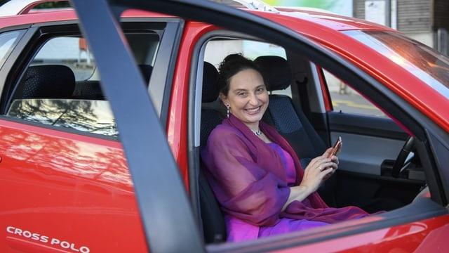 eine Frau mit eleganter Kleidung sitzt in einem Auto