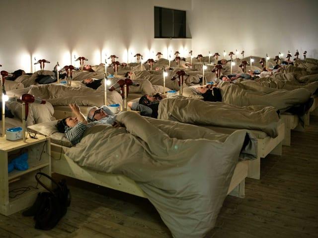 Leute liegen in Betten im Museumsaal.