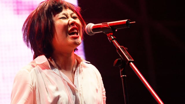 Eine Frau singt mit voller Wucht ins Mikrofon.