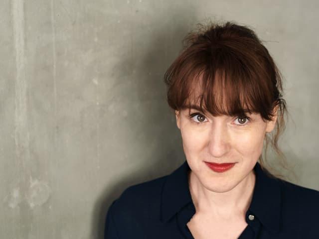 Porträtfoto der Autorin Nora Bossong vor einer grauen Wand.