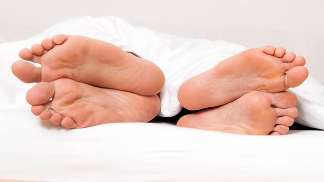 Zwei Paar nackte füsse schauen unter der weissen Bettdecke hervor.