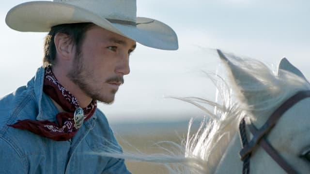 Junger MAnn mit Cowboyhut auf einem Pferd