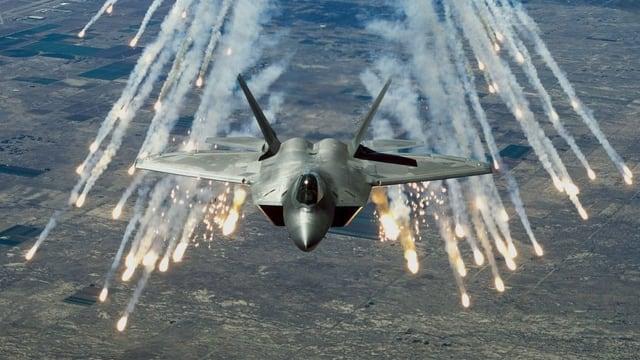 Ein Kampfjet feuert hell aufblitzende Flugkörper ab
