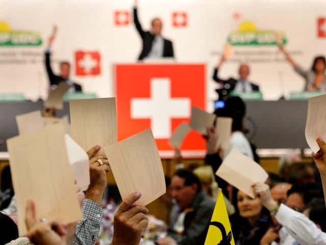 Mann auf einem Podest mit Schweizer Flagge, vorne Hände mit Zetteln.