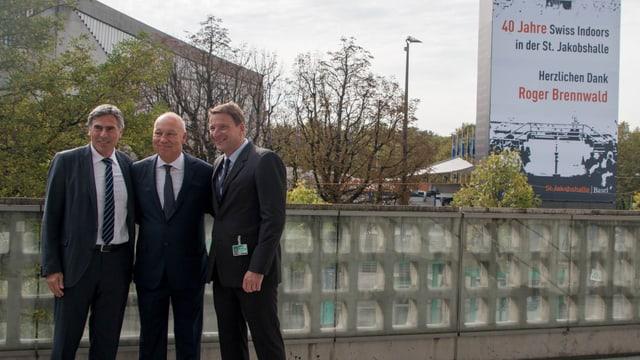 Christoph Eymann, Roger Brennwald und Thomas Kastl vor der Joggeli-Halle. Im Hintergrund das grosse Transparent mit den Dankesworten an Roger Brennwald