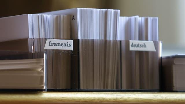 Stapel mit Informationen in Französisch und Deutsch als Symbol für den Röstigraben.