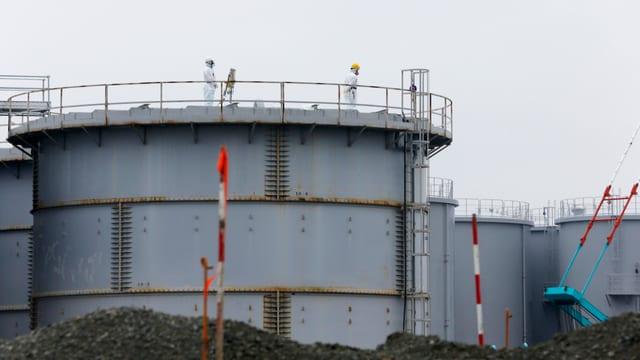 Arbeiter in Schutzkleidung arbeiten an einem Tank mit radioaktivem Material