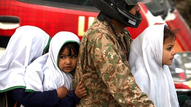 Ein Vater in Uniform bringt seine drei Töchter mit dem Motorrad zur Schule.