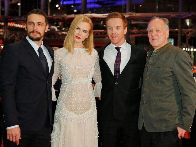 Die Darsteller und der Regisseur in Abendkleidung auf dem roten Teppich.