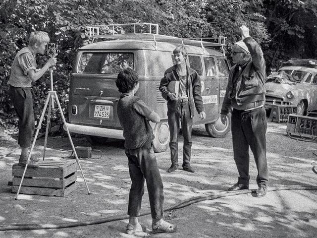 Schwarzweiss-Foto, drei Jungen und ein älterer Mann auf einem Filmset