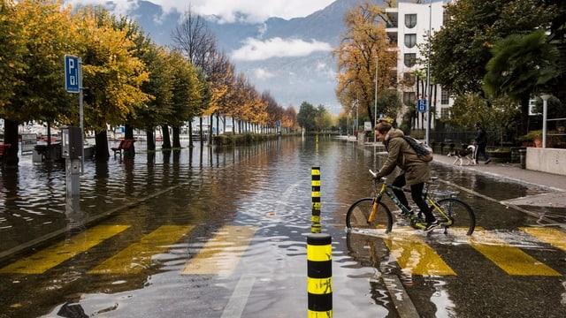 Faru mit Velo fäht auf überschwemmter Strasse in Locarno.