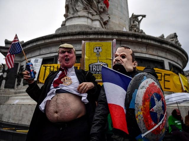 Verkleiderte Menschen protestieren.