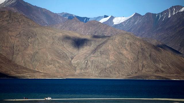 See im Vordergrund, im Hintergrund sind hohe Berge erkennbar.