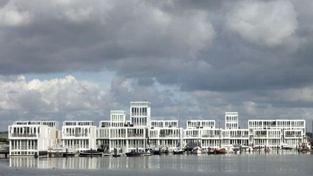 Aneinandergereihte, schwimmende Wohnungen auf dem Fluss in Amsterdam.