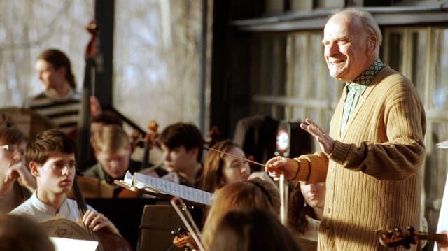 Ein älterer Herr dirigiert stehend ein Jugendorchester.