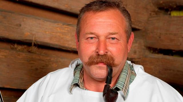 Ein Mann mit dickem Schnurrbart raucht Pfeife.