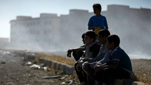 Mehrere Knaben sitzen auf einer Mauer. Im Hintergrund eine trostlose Gegend.