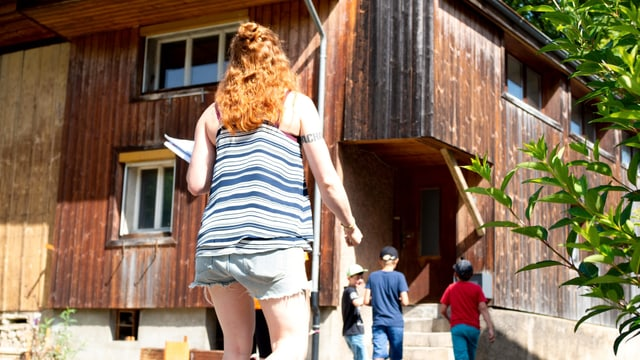 Frau läuft auf Holzgebäude zu