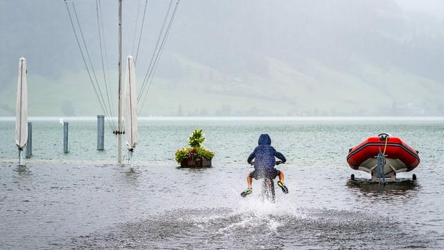 Ein Kind fährt mit seinem Velo durch das Wasser am Ägerisee.