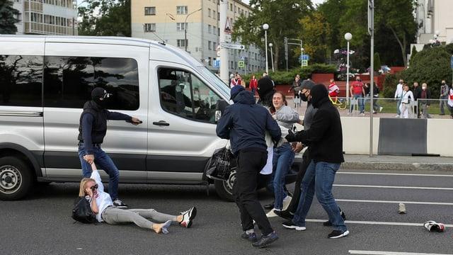 Protestierende werden weggetragen.