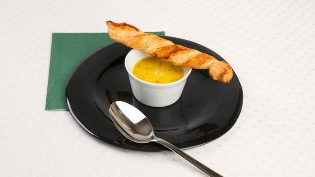 Chasselas-Suppe in weissem Schüsselchen mit Blätterteiggebäck auf schwarzem Teller angerichtet
