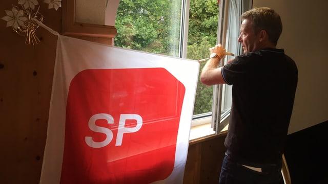 Ein Mann hängt eine SP-Transparent an ein Fenster.