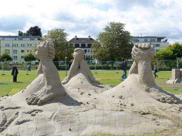 Ein paar Sandskulpturen zeigen ausgestreckte und verschränkte Arme und Hände.