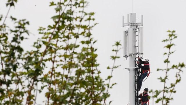 Ein Arbeiter erstellt eine Mobilfunkantenne.