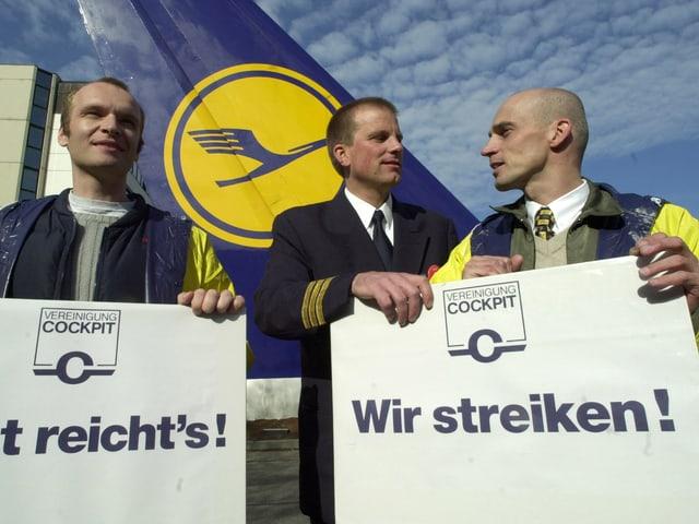Piloten mit Plakaten, auf denen «Jetzt reichts!» steht.