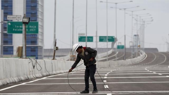 Bauarbeiter verlegt Kabel auf Strassenabschnitt