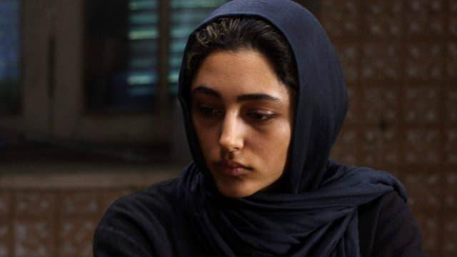 Eine Frau mit dunklem Kopftuch blickt zur Seite.