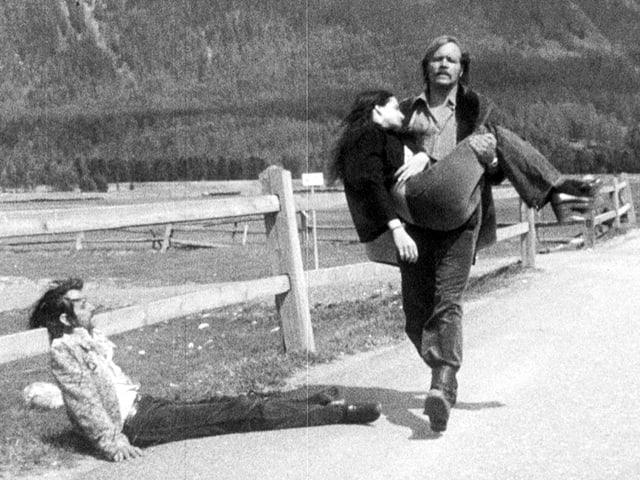 Ein Mann trägt eine ohnmächtige Frau eine Strasse entlang, am Strassenrand lehnt ein Mann leblos an ein Geländer.