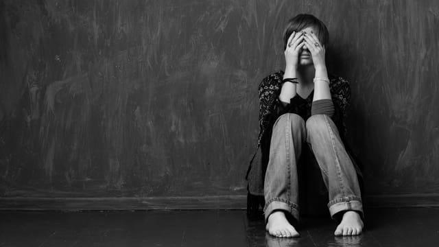 Symbolbild. Frau lehnt sich an Wand, Beine angezogen, bedeckt Gesicht mit Händen