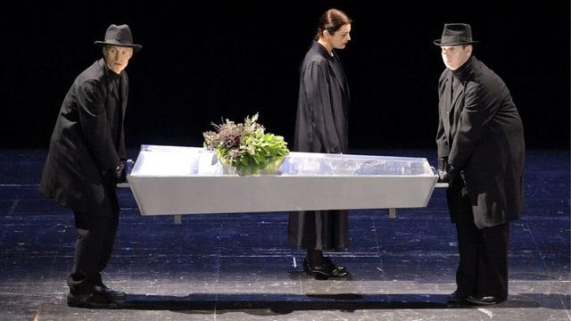 Zwei Männer auf einer Bühne tragen einen Sarg.