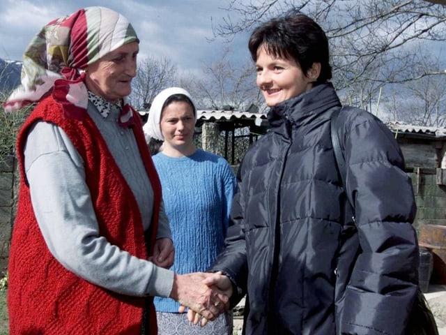 Die damalige Justizministerin Ruth Metzler schüttelt die Hand einer Frau, April 200 im Dorf Mushtisht.