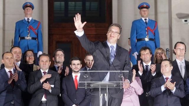 Vucic winkt von einem Podium, hinter ihm stehen die Ministerinnen und Minister.