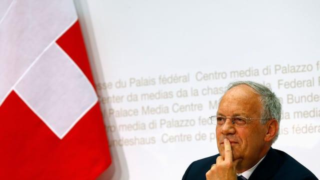 Bundesrat Johann Schneider-Ammann neben Schweizer Flagge.