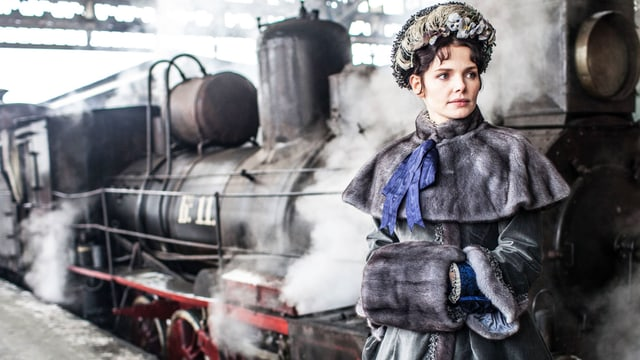 Anna Karenina steht vor einem Zug.