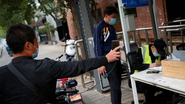 Der Fahrer eines Lieferdiensts präsentiert sein seine Gesundheitscode auf seinem Smartphone an einem Kontrollpunkt in Peking.