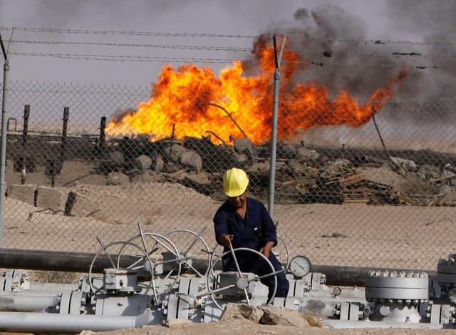 Mann in gelbem Helm bei der Arbeit auf einem Ölfeld in der Wüste.