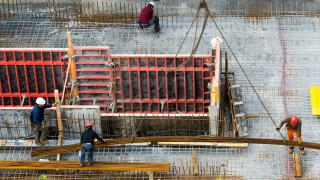 Blick auf eine Baustelle von oben, auf der Arbeiter Armierungseisen legen.