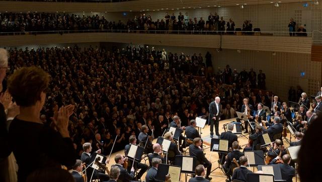 Voller Konzertsaal, auf der Bühne ein Orchester