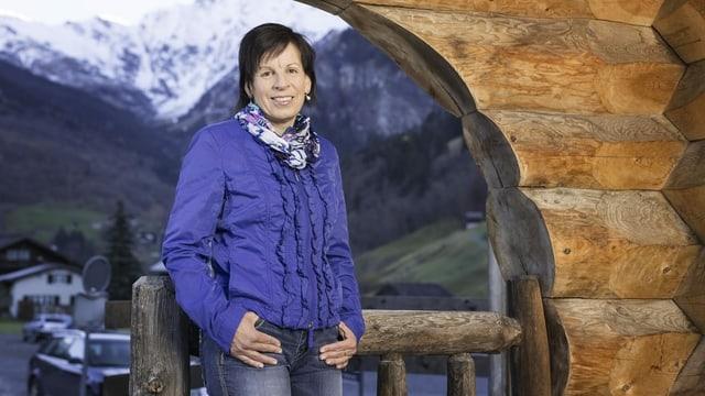 Frau in blauer Jacke vor Stalltor und Bergpanorama.