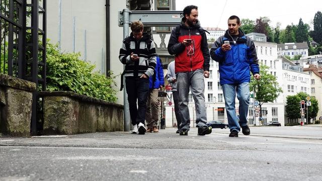 Die Gruppe zieht durch die Strassen von St. Gallen. Ihr Telefon haben sie immer im Blick.