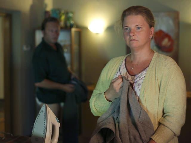 Eine Frau hält ein Stück Kleidung. Sie steht am Bügelbrett und blickt ins Nichts. Hinter ihr steht ein Mann.