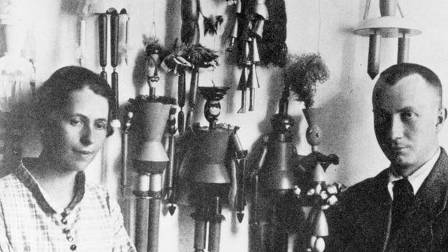 Sophie Tauber und Hans Arp stehen vor einer Wand mit Marionetten.
