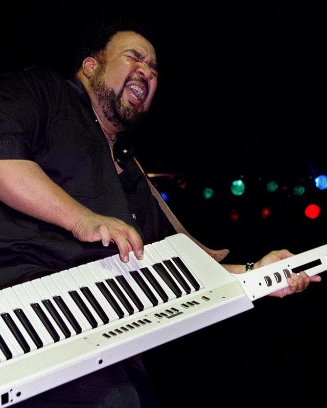 Ein schwarzer Musiker mit umgehängtem weissen Synthesizer.
